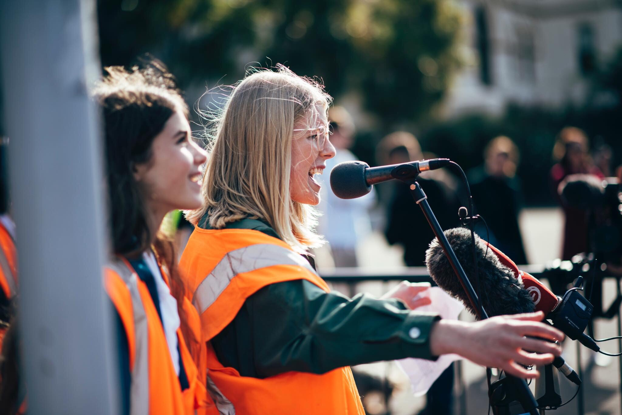 Young woman wearing high vis vest speaking to crowd
