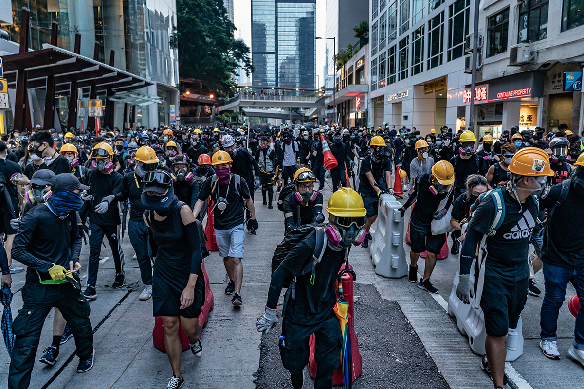 People in black clothing and yellow safety helmets walk down street dragging supplies