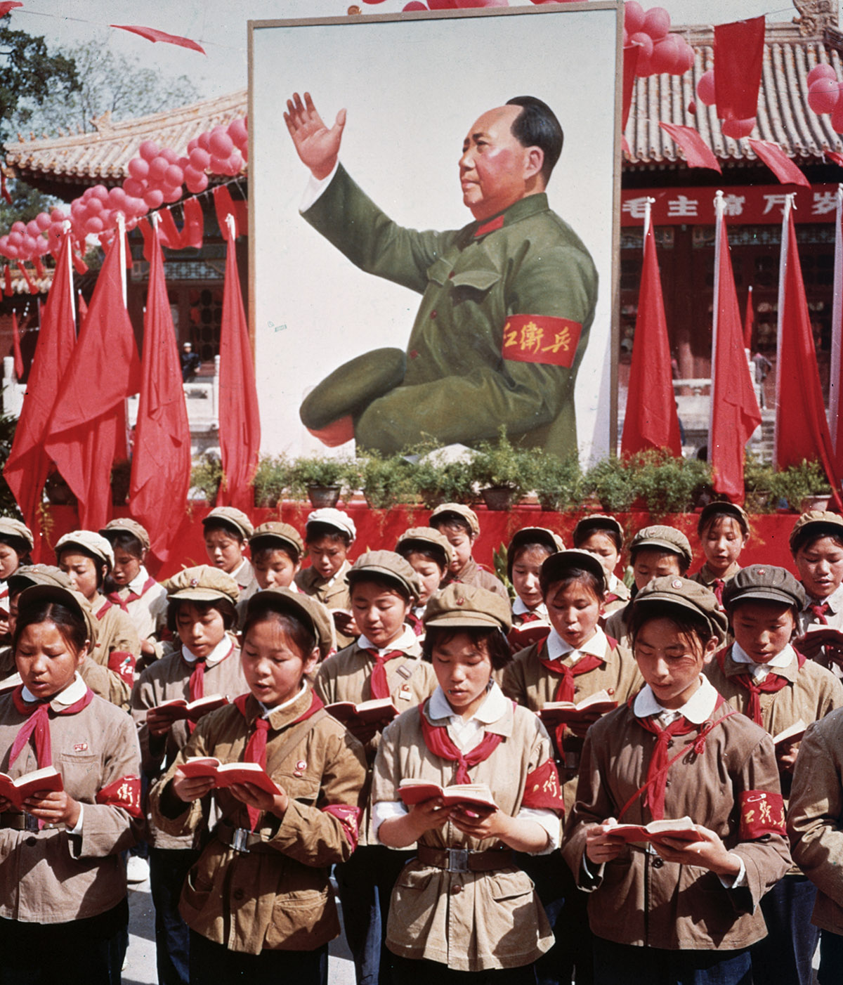 Children in uniform standing in rows, holding red booklets in front of painting of Mao Zedong
